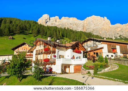 Traditional alpine houses with flowers on balcony, San Cassiano, Dolomites Mountains, Italy - stock photo