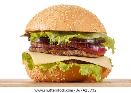 Traditional American cheeseburger. Meat, bun and vegetables close up on white background