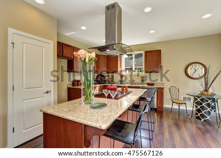 Traditional American kitchen featuring stainless steel appliances, range hood, an island and granite countertops. Northwest, USA