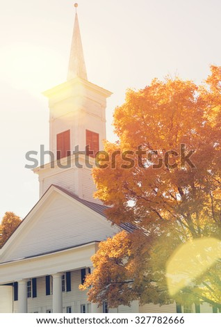 Traditional American white church in the fall with nautural sun flare - stock photo