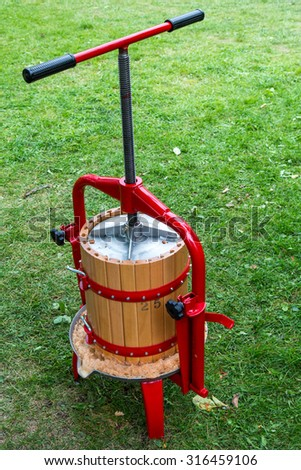 Traditional apple press made from a small wooden barrel and a metal screw press - stock photo