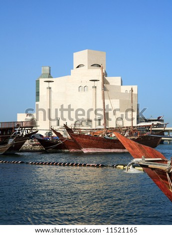 Traditional Arab dhows moored in the harbour beside the Museum of Islamic Art in Doha, Qatar. April 2008 - stock photo