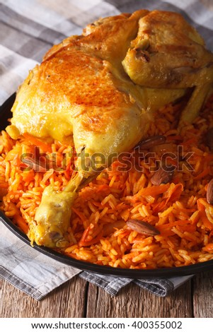 Traditional Arabic food: kabsa with chicken and almonds close-up on a plate. vertical