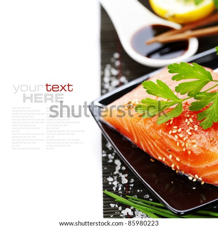 traditional asian ingredients (Fresh salmon steak filet, lemon and soy sause) with chopsticks over white with sample text - stock photo