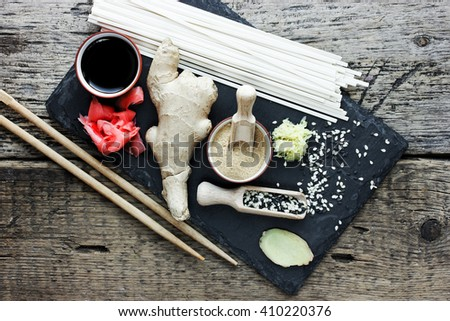 Traditional asian ingredients ginger root, pickled ginger, dried ginger, black and white sesame seeds, udon noodles, soy sauce on a stone plate on the old wooden background top view - stock photo
