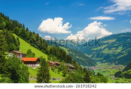 Traditional Austrian alipine hous on green grass hill in Zillertal alpine valley against blue sky, Insbruck area, Austria - stock photo