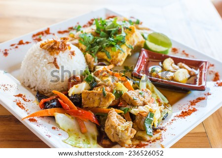Traditional Balinese cuisine. Vegetable and chicken stir-fry with rice. - stock photo