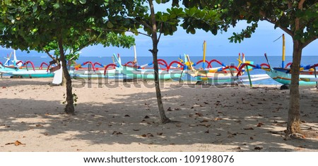 Traditional Balinese outrigger style wooden fishing boats in a line on the beach at Sanur, Bali, Indonesia. Tropical trees in the foreground. - stock photo