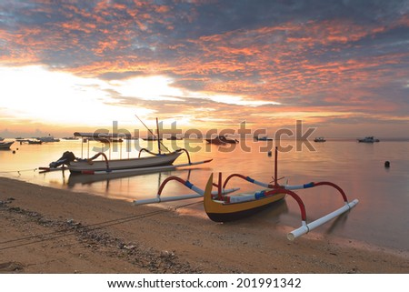 traditional Balinese ships Jukung close on Sanur beach at sunrise, Bali, Indonesia - stock photo