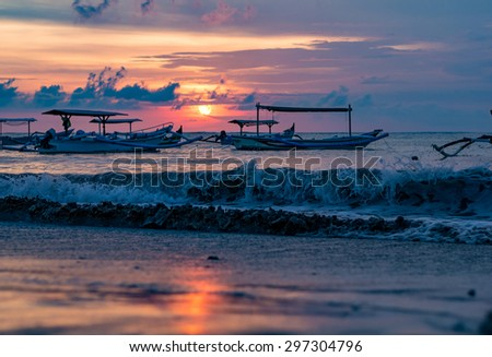 traditional Balinese ships Jukung close on Sanur beach at sunrise, Bali, Indonesia - stock photo