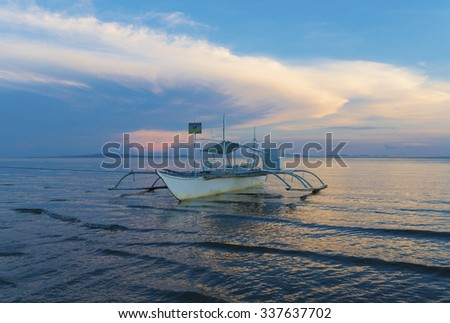 traditional bangka boat on a philippine beach during a beautiful sunset - stock photo