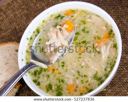 traditional barley soup with meat in a white bowl