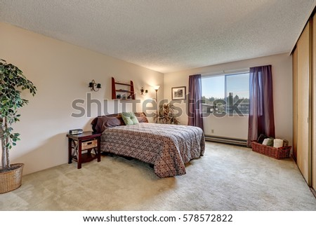 Traditional bedroom with warm beige walls paint color, brown white bed paired with brown window curtains. Northwest, USA