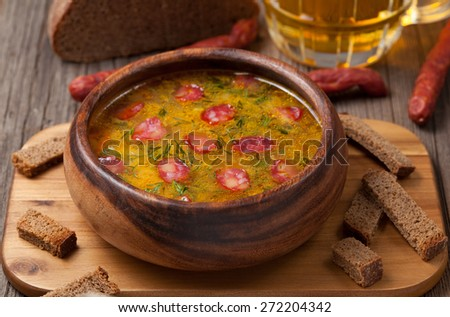 Traditional beer soup with cheese sausage dill croutons and beer on vintage background - stock photo