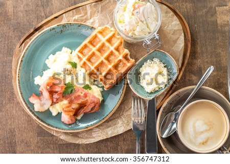 Traditional Belgian waffles with scrambled eggs and bacon on wooden table - stock photo