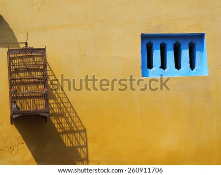 traditional bird cage on the yellow wall          - stock photo