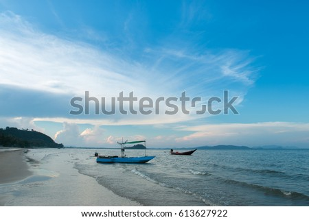Traditional blue wooden fishing boats in the ocean at sunset