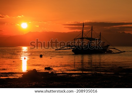 Traditional boats and mountains in silhouette against a tropical sunset - stock photo