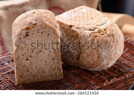 Traditional bread on old wooden basket - stock photo