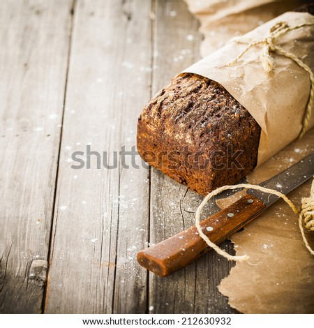 Traditional bread with seeds wrapped in paper on old wooden table - stock photo