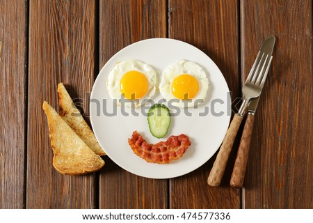 Traditional breakfast - eggs, bacon, toast and vegetables, fruit