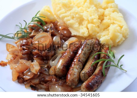 """Traditional British """"bangers and mash"""" fried sausages with onions and mashed potatoes. - stock photo"""
