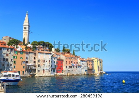 Traditional buildings and church of an old Venetian town sided by the blue water of Adriatic sea, Rovinj, Croatia - stock photo