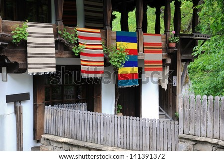 Traditional Bulgarian woven fabrics on the balcony of the wooden house in Etar village - stock photo