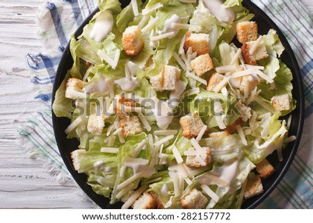 Traditional Caesar salad with croutons and parmesan close-up on a plate. horizontal top view  - stock photo