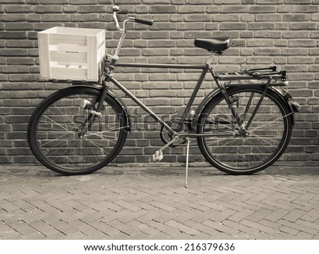 traditional cargo bike with crate viewed side on against a brick wall. toned black a white.