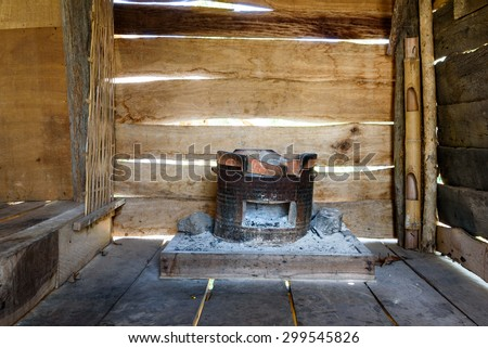 Traditional charcoal burning clay stove in a rustic wooden house. - stock photo