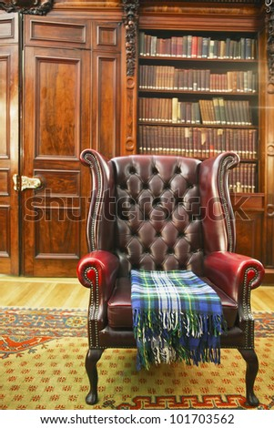 Traditional Chesterfield armchair with tartan blanket in classical library room