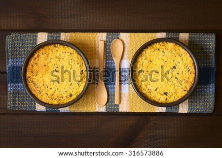 Traditional Chilean Pastel de Choclo corn pie in rustic bowls, photographed on dark wood with natural light. Below the corn-basil mix is ground meat, olive, boiled egg, raisin, pieces of chicken.    - stock photo