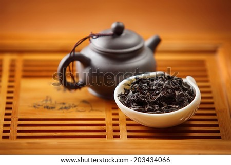 traditional chineese black tea leaves and teapot - stock photo