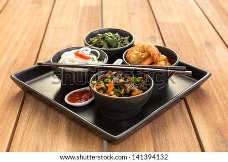 Traditional chinese dish on a square plate in black bowls with shrimp, rice noodles, kale (green cabbage) and fried vegetables. Composed with ceramic spoon with spicy red sauce and chinese chopsticks. - stock photo