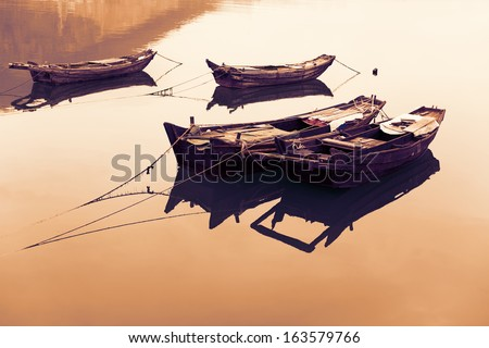 Traditional Chinese fishing boats out of wood on the lake. - stock photo