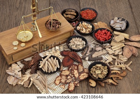 Traditional chinese herb ingredients used in alternative herbal medicine with old brass scales over bamboo and oak background. - stock photo