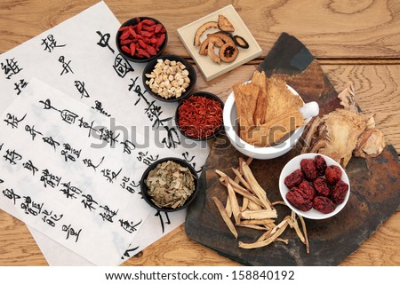 Traditional chinese herbal medicine selection with mandarin calligraphy on rice paper over oak. Translation describes the medicinal functions to maintain body and spirit health and balance energy. - stock photo
