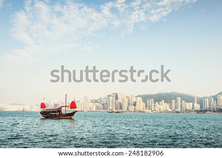 Traditional Chinese Junkboat sailing. Hong Kong. Views of the skyscrapers background.