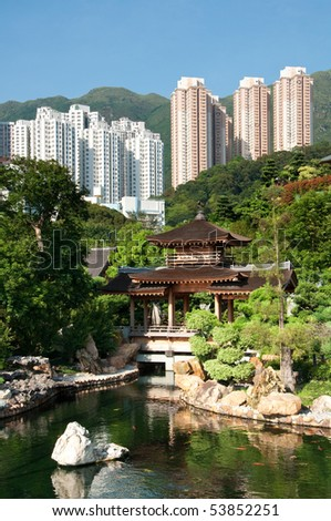 Traditional Chinese Pagoda in a garden setting contrasts with the modern skyscrapers on the hill behind. - stock photo