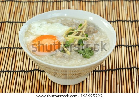 Traditional chinese porridge rice gruel in bowl with pork and Boiled egg