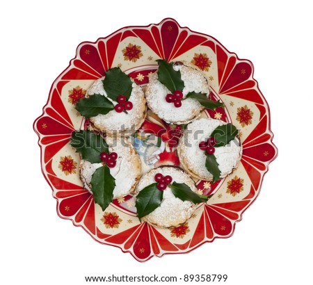 Traditional Christmas English mince pies decorated with icing sugar and holly with berries.  On an attractive  old fashioned cream and red plate. Isolated on white. - stock photo