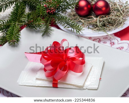 Traditional Christmas Eve white wafer on a plate with red cockade - stock photo