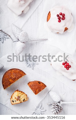 Traditional Christmas Fruit Cake in a sugar glaze  with marzipan and cranberry decor on a Christmas decoration background.selective focus. - stock photo