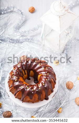 Traditional Christmas Fruit Cake in chocolate coating with nuts decor on a Christmas decoration background.selective focus. - stock photo