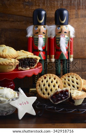Traditional Christmas fruit mince pies spotlighted in festive setting with rustic style gifts and decorations on dark vintage wood background.  - stock photo