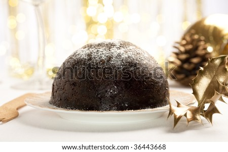 traditional christmas pudding with golden decorations, shallow DOF - stock photo