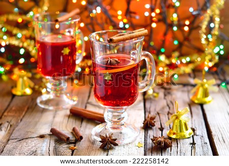 Traditional Christmas punch with spices such as cinnamon and star anise in a glass cups decorated with golden stars - stock photo