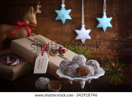 Traditional Christmas Rum Ball candy spotlighted in festive setting with rustic style gifts and decorations on dark vintage wood background.  - stock photo