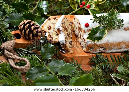 Traditional Christmas stollen surrounded by Christmas decorative green twigs
